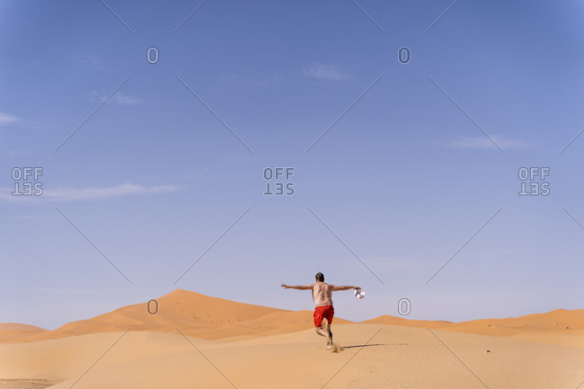 Overweight man with swimming shorts running in the desert of Morocco