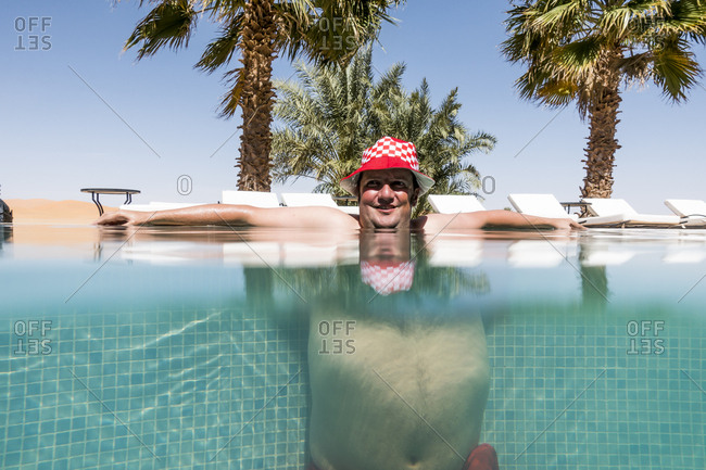 Overweight man with hat bathing in pool