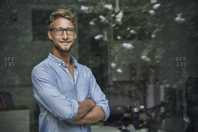 Portrait of casual young businessman behind windowpane in office