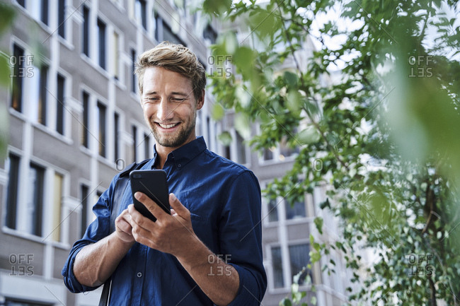 Smiling young businessman using mobile phone in the city