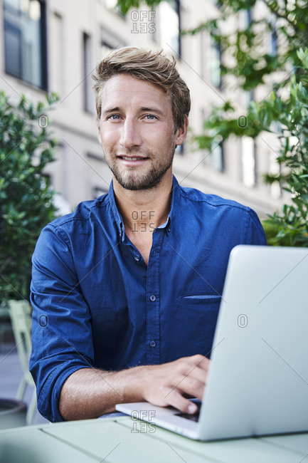 Portrait of young businessman with laptop at an outdoor cafe in the city