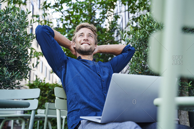 Young businessman with laptop at an outdoor cafe in the city having a break