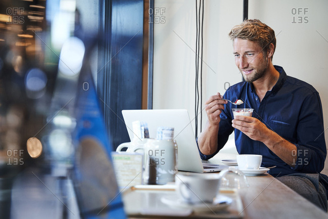 Young businessman eating and using laptop in a cafe