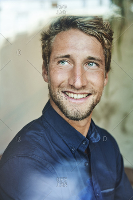 Portrait of smiling young man behind windowpane