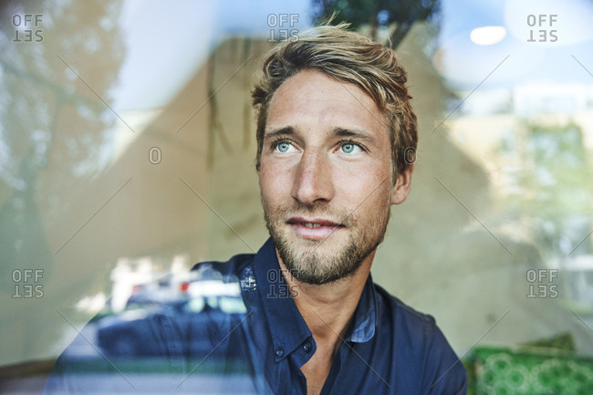 Portrait of young man behind windowpane