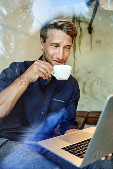 Young businessman drinking coffee and using laptop in a cafe