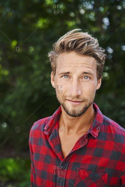 Portrait of confident young man wearing checkered shirt outdoors