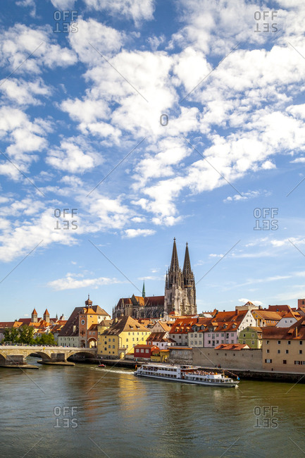Ferry moving on Danube River by St. Peter's Church in Regensburg against sky