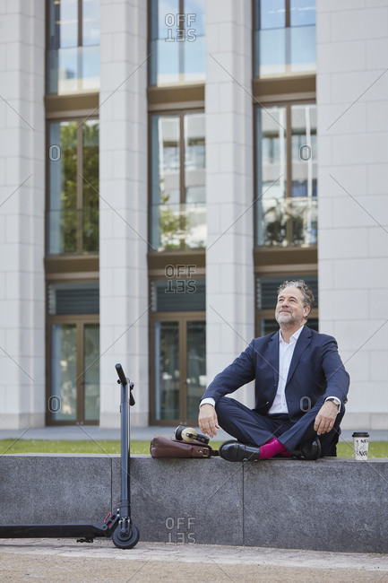 Relaxed mature businessman sitting on wall in the city