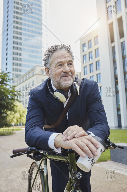 Mature businessman with bicycle and takeaway coffee in the city