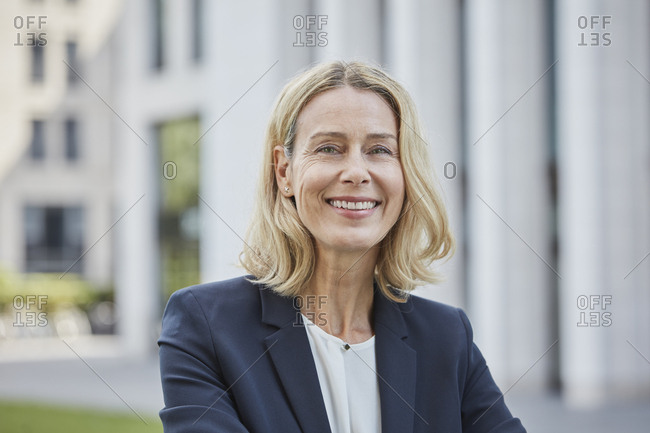 Portrait of smiling blond businesswoman in the city