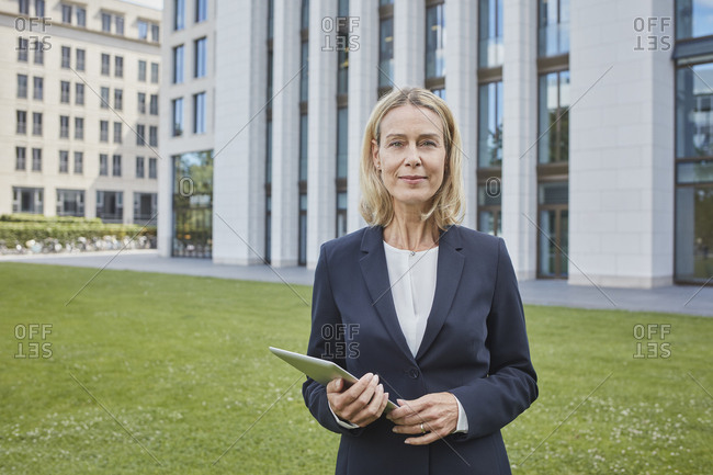 Portrait of confident businesswoman with tablet standing on lawn in the city