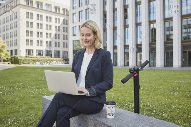 Businesswoman sitting on a wall in the city using laptop