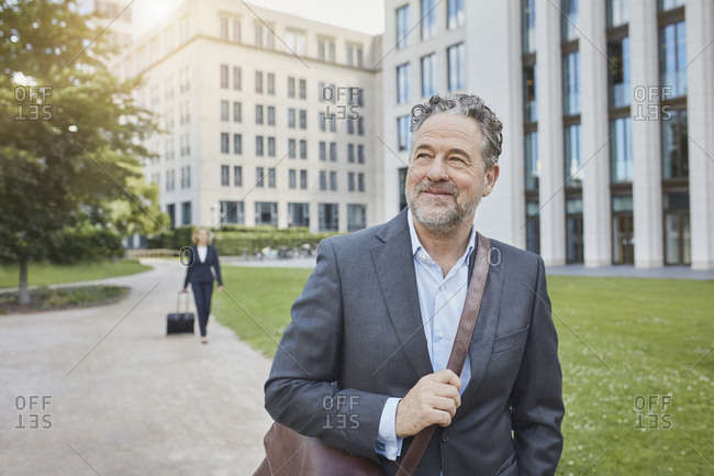 Portrait of smiling businessman in the city with businesswoman in background
