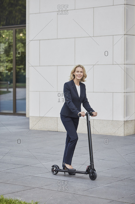 Businesswoman on e-scooter standing before office building in the city