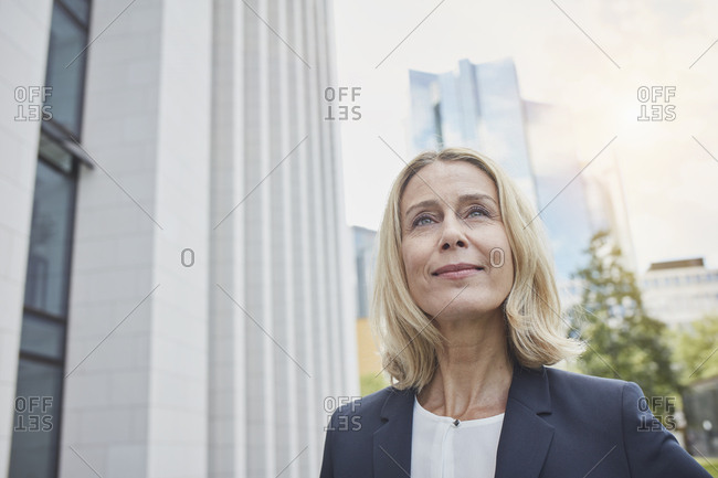Portrait of confident blond businesswoman in the city looking up