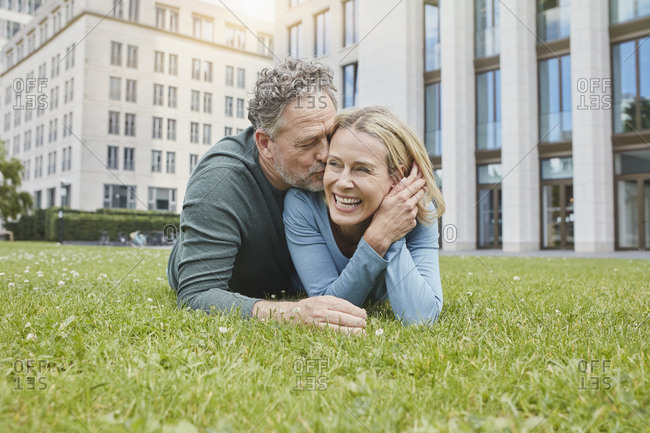 Happy mature couple lying on lawn in the city