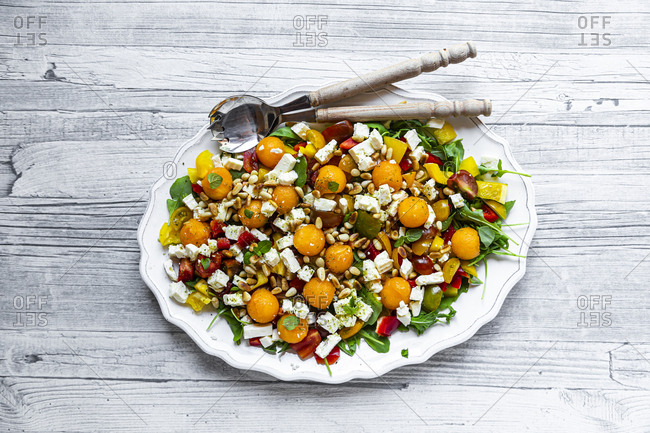 High angle view of healthy salad with spoons in plate on wooden table