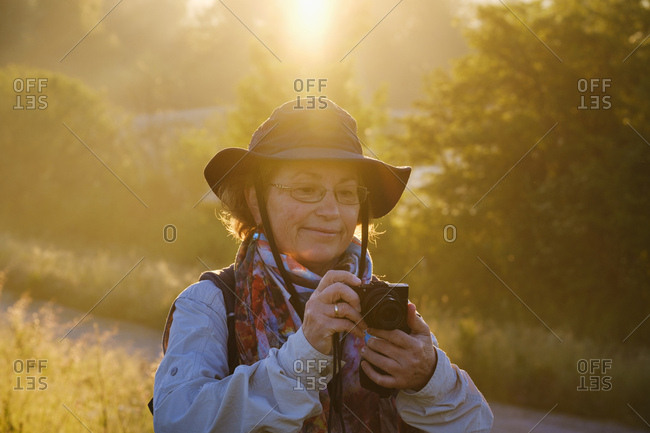Senior female hiker looking at camera while standing in forest