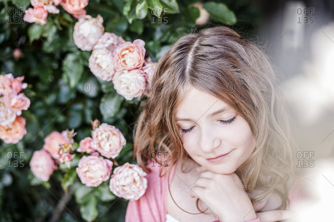 Portrait of girl with eyes closed beside pink rosebush