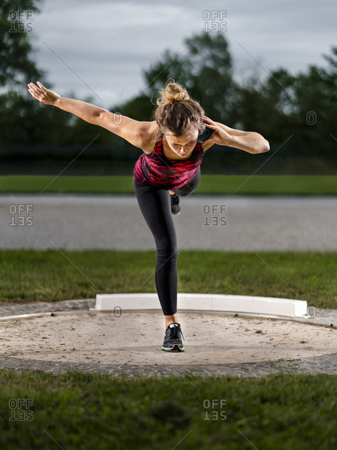 Female shot-putter training with ball
