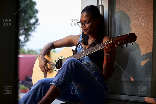 Woman playing guitar sitting at the edge of the window