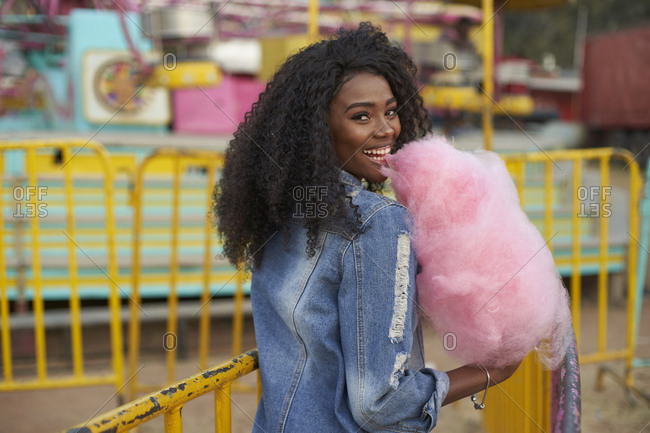 Portrait of happy young woman with pink candy floss at fair