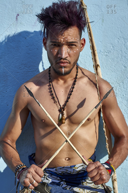 Tribal man with his traditional arch and arrows leaning on blue wall- Lubango- Angola
