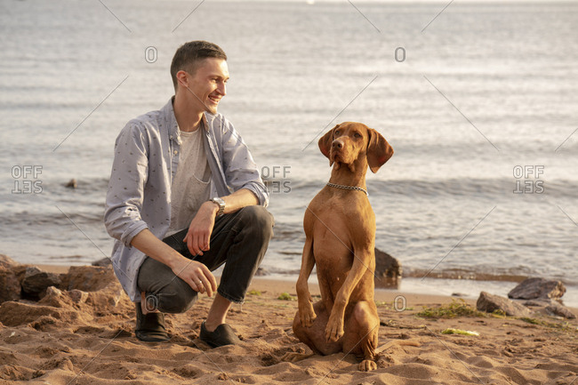 Young man with his dog at the beach during training