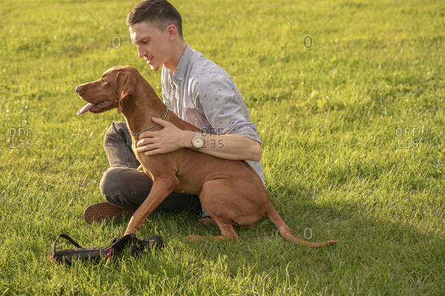 young man with his dog- cuddling on a meadow