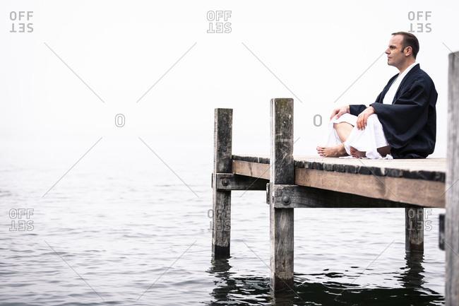Man sitting on jetty doing yoga exercise- Lake Starnberg- Germany