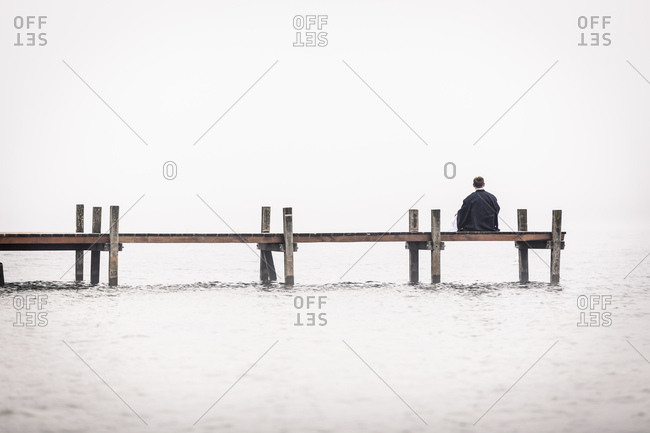 Back view of man sitting on jetty at Lake Starnberg- Germany