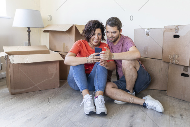 Happy couple using cell phone in new home
