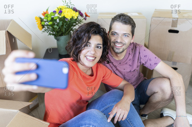 Happy couple taking a selfie in new home