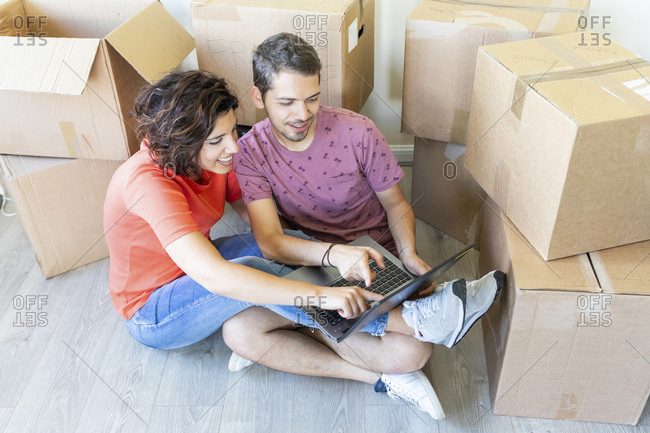 Happy couple moving into new home using laptop