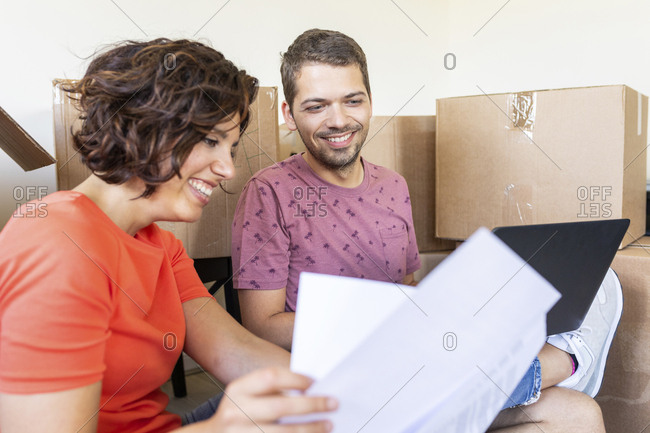 Happy couple in new home with documents and laptop