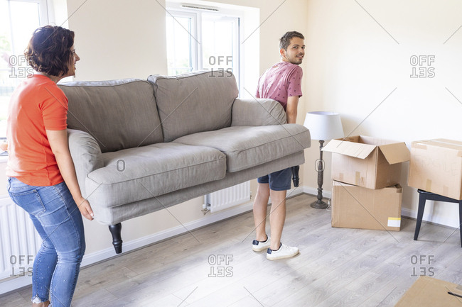 Couple moving into new home carrying a sofa