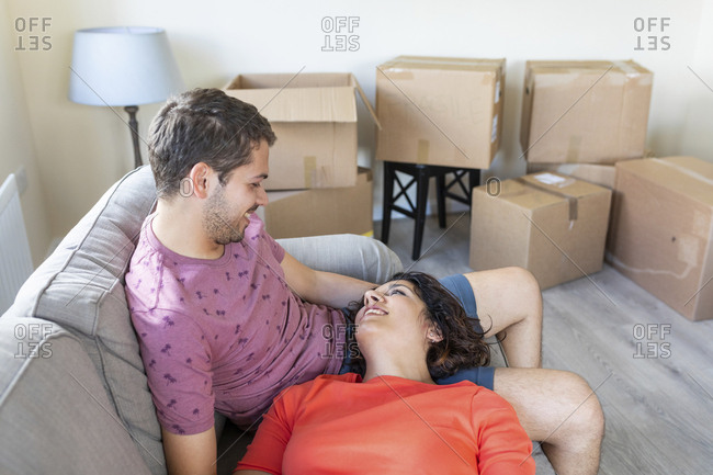 Happy couple relaxing on couch in new home