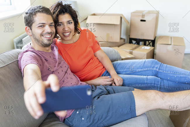 Happy couple taking a selfie on couch in new home