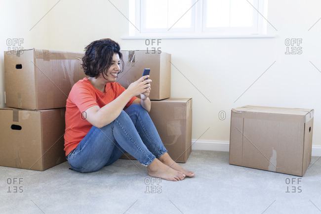 Woman sitting on the floor in new home using cell phone