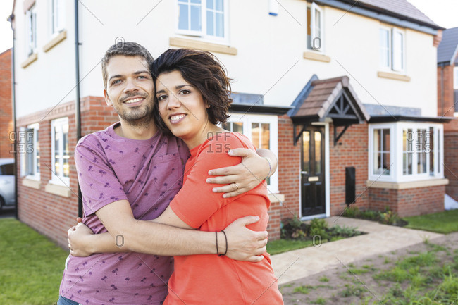 Portrait of happy couple hugging in front of their new home