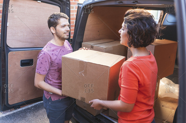 Couple unloading cardboard boxes from van