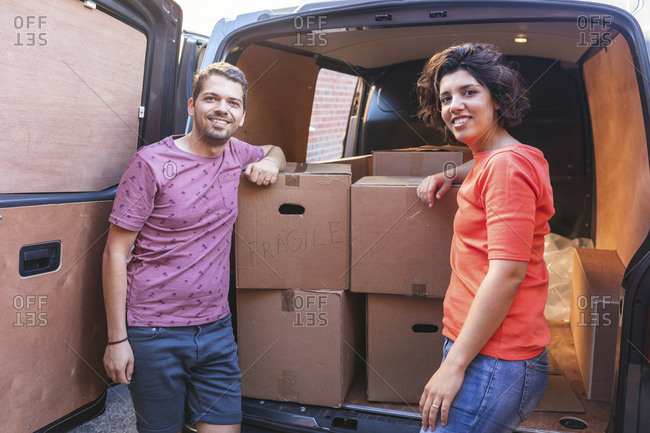 Portrait of smiling couple at van with cardboard boxes
