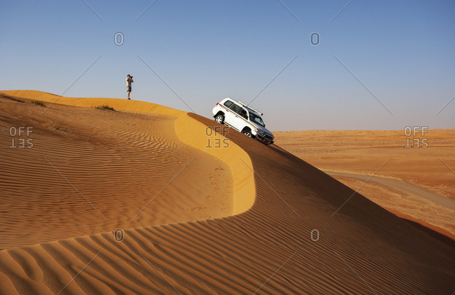 Man with off-road vehicle- taking pictures in the desert- Wahiba Sands- Oman
