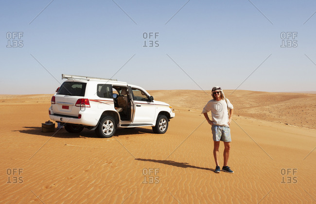 Tourist standing in the desert next to off-road vehicle- Wahiba Sands- Oman
