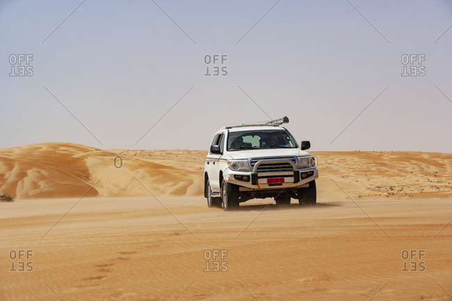Tourist driving in desert in off-road vehicle- Wahiba Sands- Oman