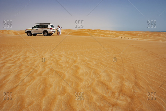 Tourist talking to his driver in the desert next to off-road vehicle- Wahiba Sands- Oman