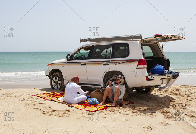 Tourist having a coffee break with his local driver at the Indian Ocean- Oman