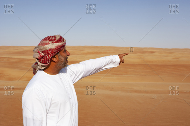 Bedouin in National dress standing in the desert- pointing at distance- Wahiba Sands- Oman