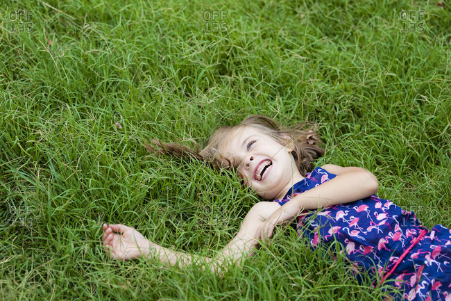 Laughing little girl lying on a meadow in summer